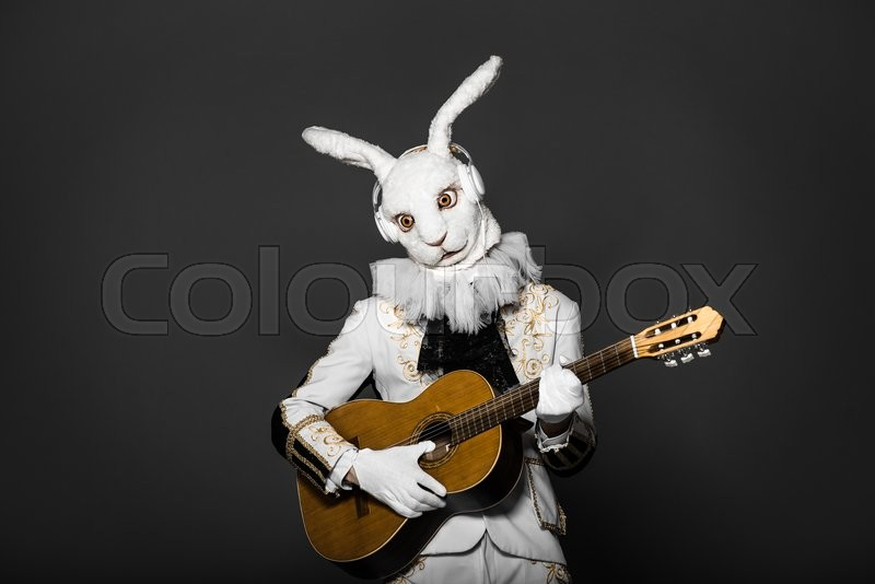Actor Posing In White Rabbit Suit Playing Guitar With Earphones On Black BackgroundStudio ShotHalloween TimeBunny Man