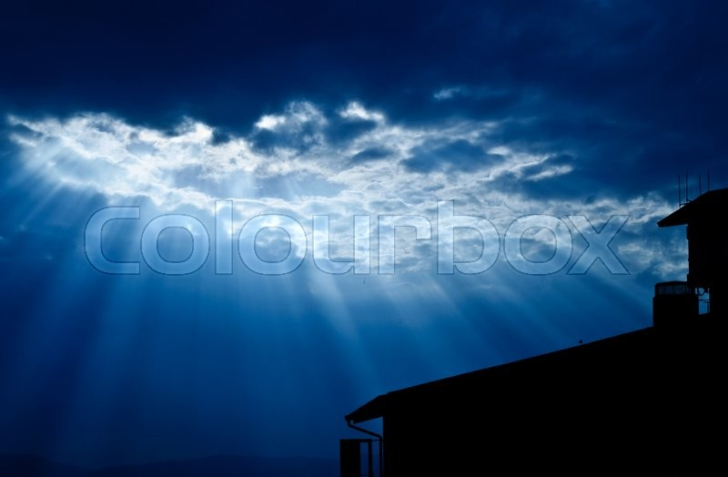 Light form the sky shining down on house / Crepuscular rays / Jesus light with house in deep blue sky, stock photo