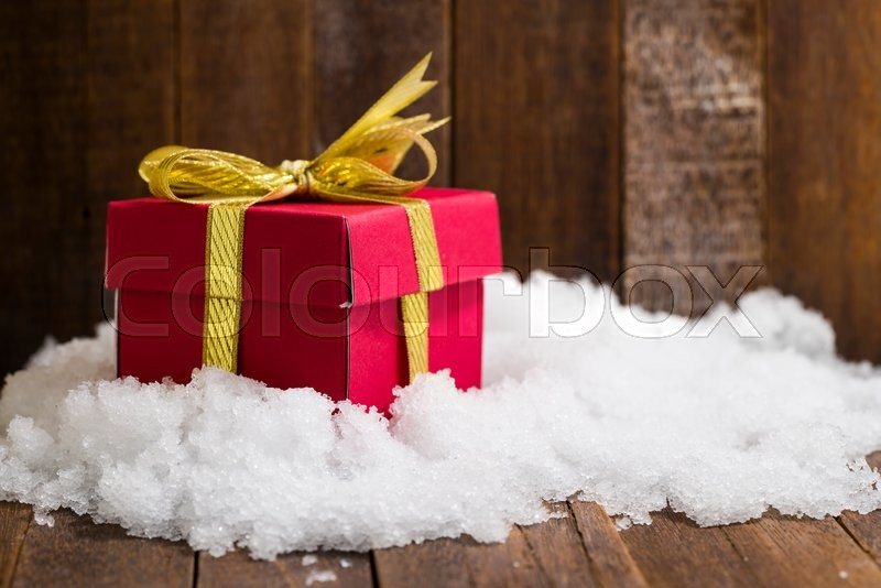 Christmas gift box with a gold ribbon bow on snow, stock photo