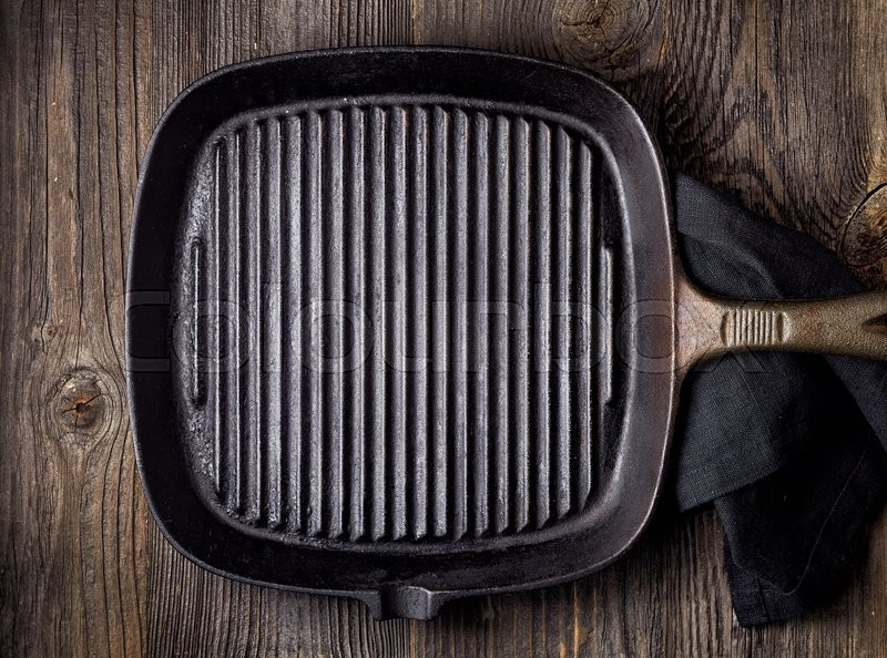 Empty black cooking pan on wooden table, top view, stock photo