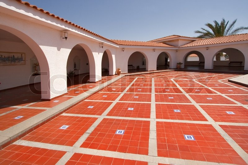 a red marble floor in a court yard in the spanish style surrounded by gallery stock photo. Black Bedroom Furniture Sets. Home Design Ideas