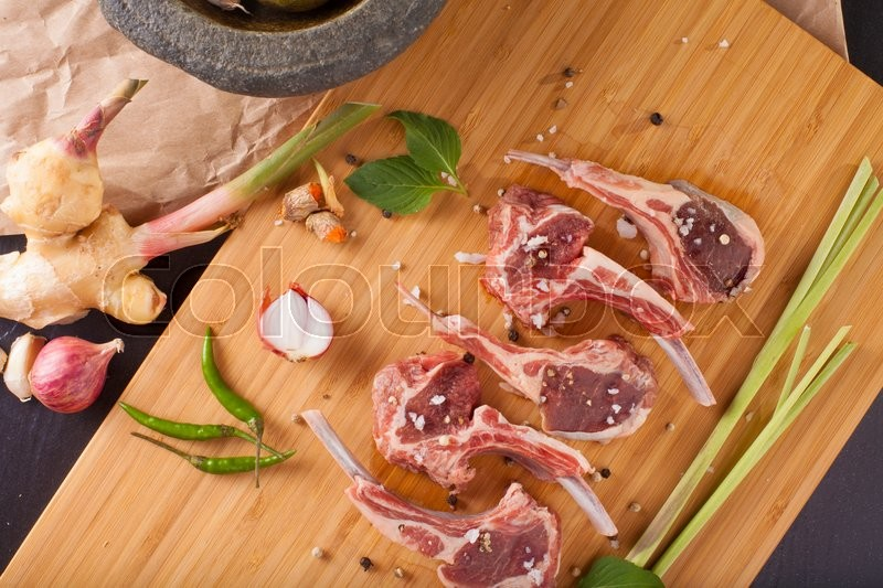 Lamb chop, Raw rack of lamb cut in pieces decorate and seasoning with rosemary tomato herbs and olive oil fork and knife on black stone, stock photo
