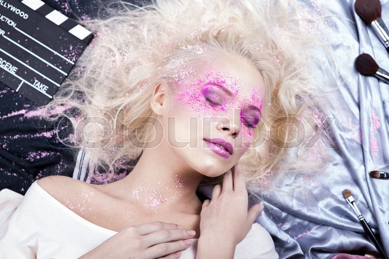 Portrait of beautiful blonde woman in white shirt with bright art color pink professional make up poses on studio background.Fashion look, stock photo