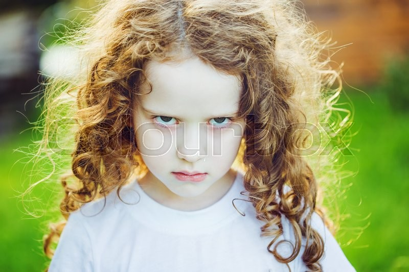 Emotional child with angry expression ...