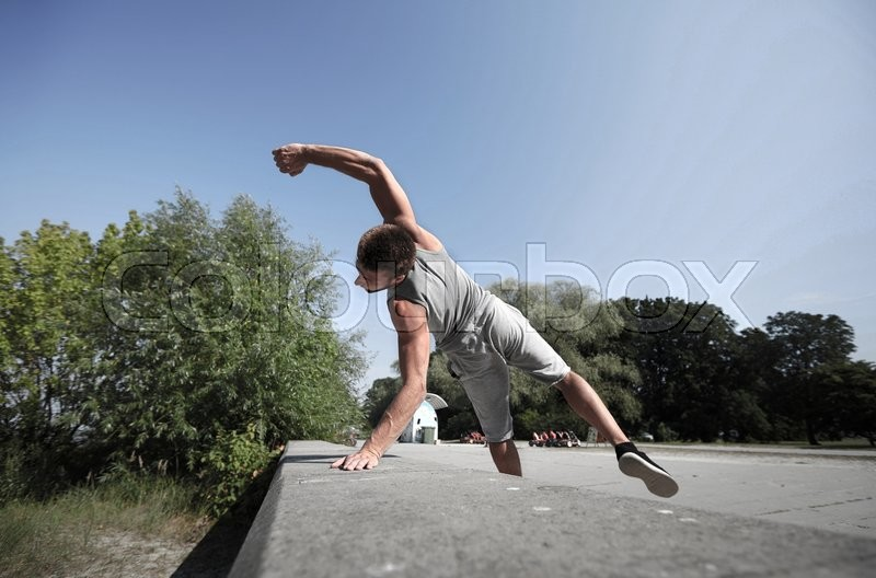 Fitness, sport, parkour and people concept - young man jumping in summer park, stock photo