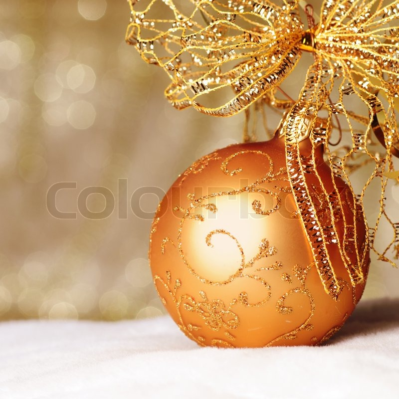 http://www.colourbox.com/preview/1528525-208333-gold-christmas-ball-and-bow-ornament-on-white-fur-of-defocused-golden-lights-shallow-dof.jpg