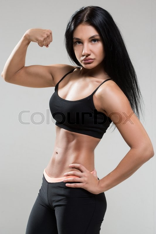Portrait of young fitness woman shows biceps. Muscular female body ...