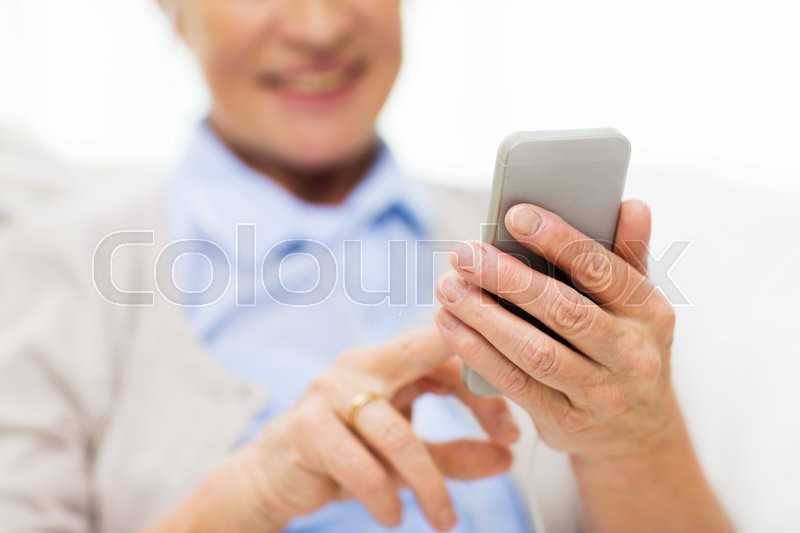 Technology, communication age and people concept - close up of happy senior woman with smartphone texting message at home, stock photo