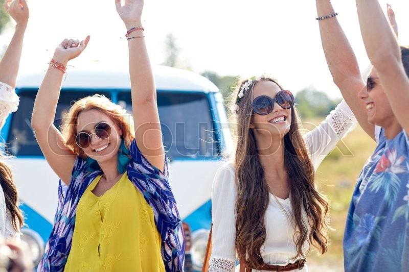 Nature, summer, youth culture and people concept - happy young hippie friends dancing over minivan car outdoors, stock photo