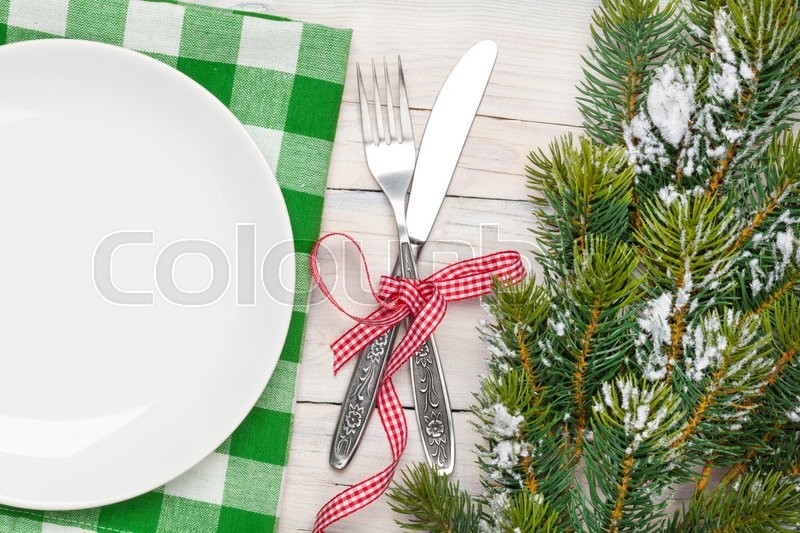 Empty plate, silverware and christmas tree. View from above over white wooden table background, stock photo