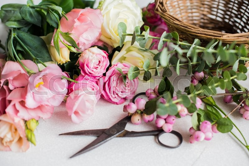Fresh flowers, leaves, and tools to create a bouquet on a table, florist\'s workplace, stock photo