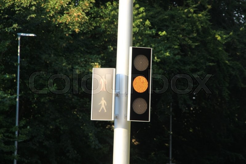 Traffic light is orange for the cars and red for the pedestrians at the intersection in the village Kolding in Denmark, stock photo