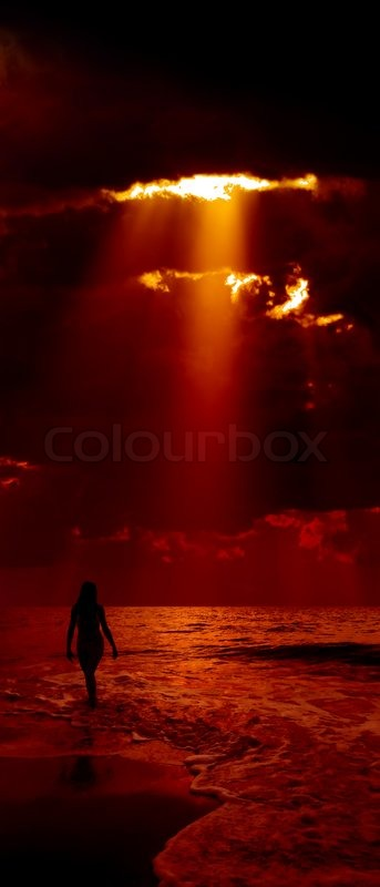 Silhouette of girl and dramatic dark red sky with sunbeam ...