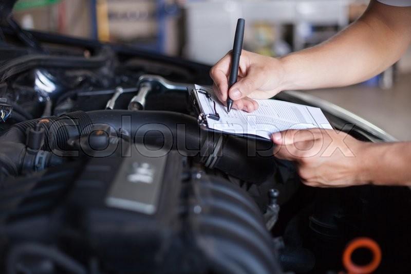 Mechanic repairman inspecting car, stock photo