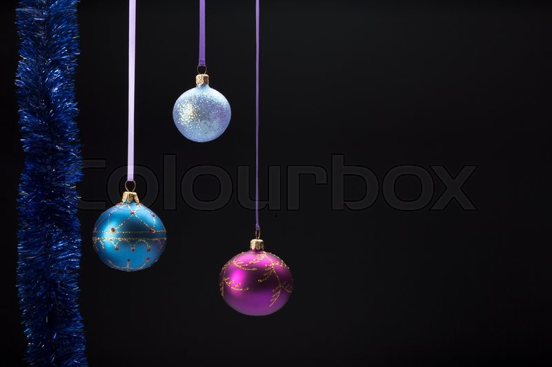 Hanging three colorful christmas balls on black background, stock photo