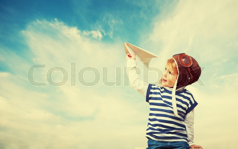 Happy child dreams of becoming a pilot aviator and plays with planes in the sky, stock photo