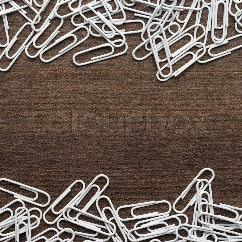 White paper clips on the wooden table with copy space, stock photo