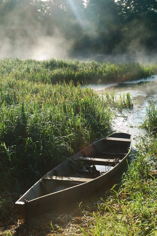 Beautiful river and old rowing boat in green grass | Stock Photo | Colourbox