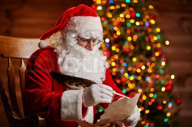 Santa Claus answering Christmas letter by sparkling firtree, stock photo