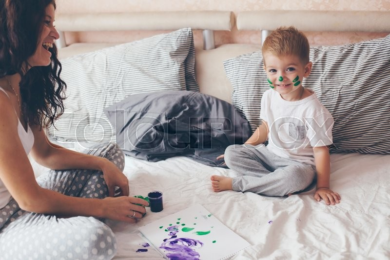 young mother with her 2 years old little son dressed in pajamas are relaxing and playing in the. Black Bedroom Furniture Sets. Home Design Ideas