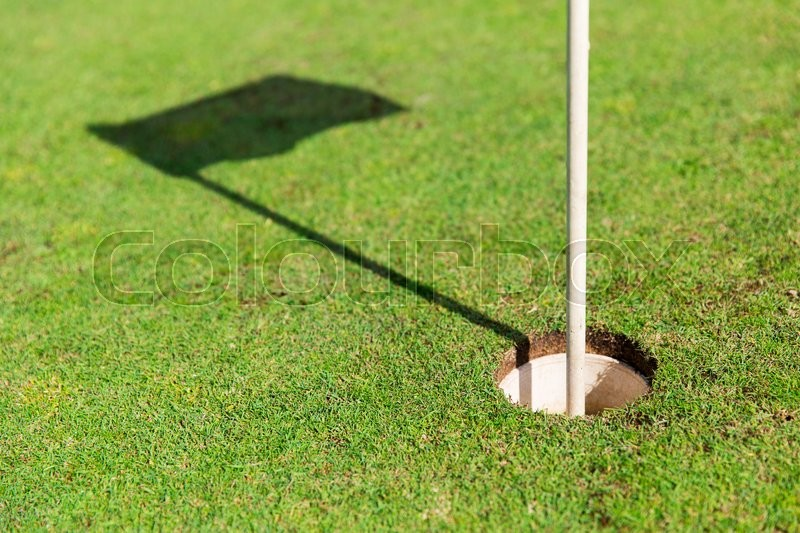 Game, entertainment, sport and leisure concept - close up of flag mark in hole on golf field, stock photo