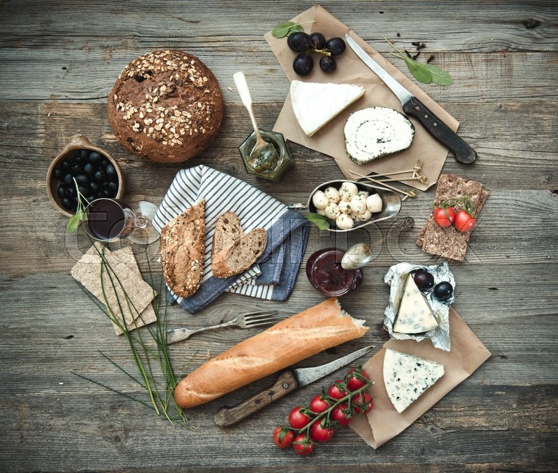 French food on a wooden background. Different types of cheese, wine and other ingredients on a wooden table, stock photo