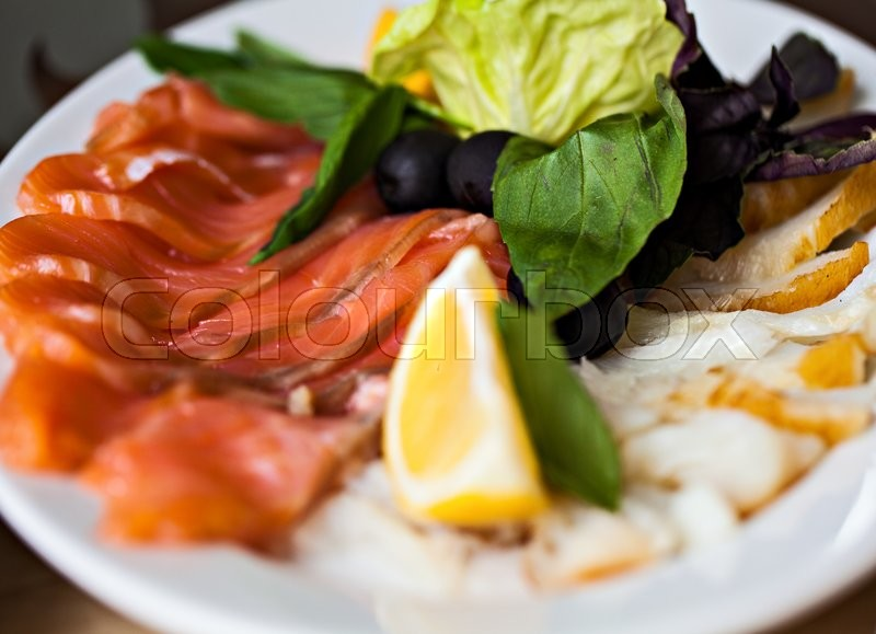 Fish appetizer with lemon and lettuce on white plate in restaurant.Healthy food.Tasty diet, stock photo