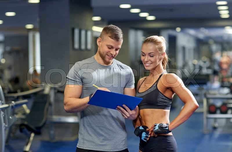 Fitness, sport, exercising and diet concept - smiling young woman and personal trainer with clipboard writing exercise plan in gym, stock photo