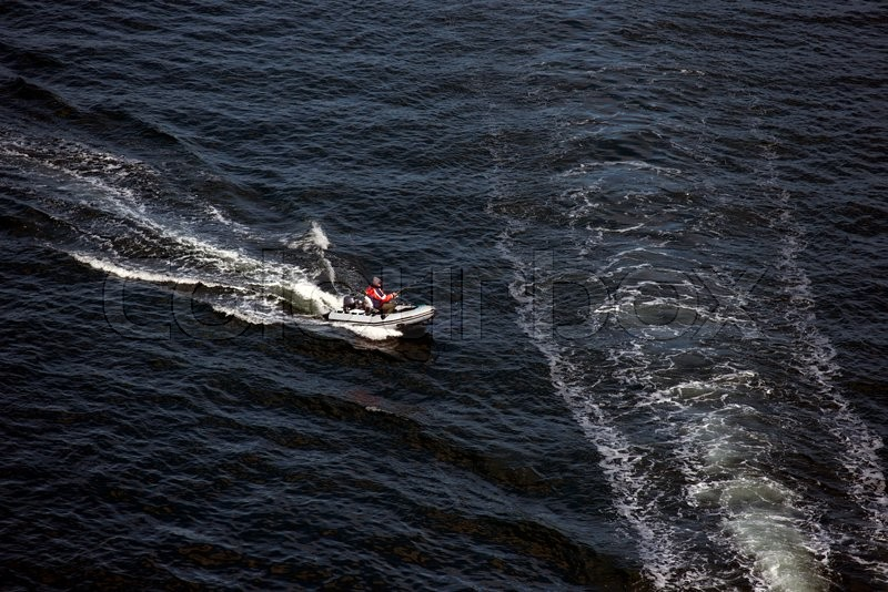 Man in a small inflatable boat are fishing in the sea ...