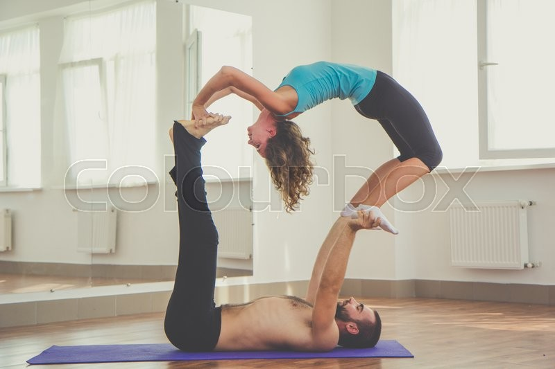 young sportive two people are practicing acro yoga exercises in the