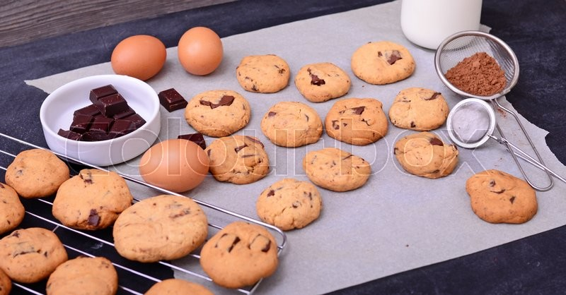 Home baked chocolate cookies and ingredients on baking paper on black background, stock photo