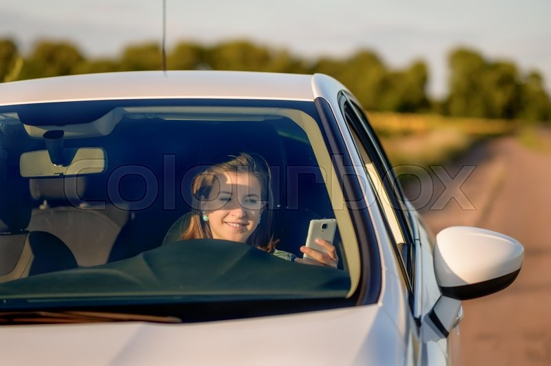 Texting While Driving >> Front View of Teenage Girl Holding Cell Phone While Driving Car on Country Road - Distracted ...