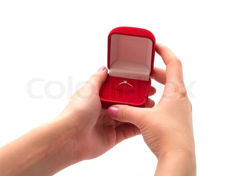 Female hand holding a red box with a gold ring isolated on a white