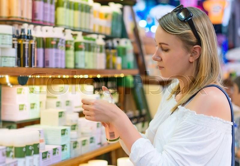Young woman choosing cosmetic cream in beauty shop, stock photo