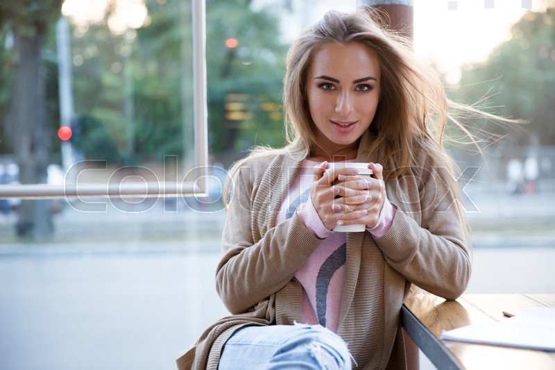 Woman Looking At A Man Drinking Coffee In A Cafe