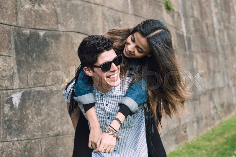 Heterosexual couple having fun. The man takes the girl astride, stock photo