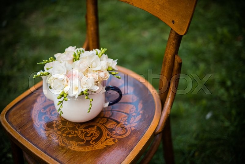 Summer wedding party festive decor, lovely fresh bouquet of white summer roses and freesias in vintage enamel tea pot on an old brown wooden chair. Retro style outdoor decoration, grass background, stock photo