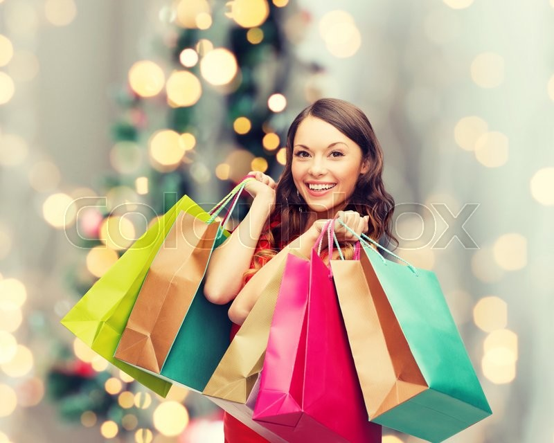 Sale, gifts, holidays and people concept - smiling woman with colorful shopping bags over living room and christmas tree background, stock photo