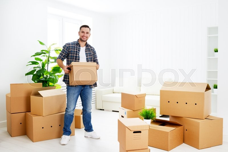 Moving to a new apartment. Young happy man with cardboard boxes, stock photo