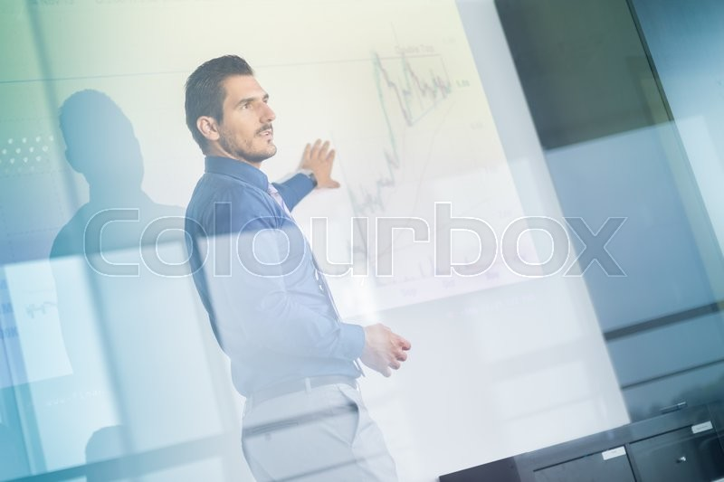 Business man making a presentation in front of whiteboard. Business executive delivering a presentation to his colleagues during meeting or in-house business training. View through glass, stock photo