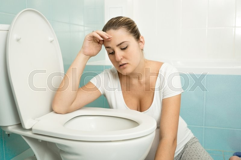 Portrait of young woman feeling sick and leaning on toilet