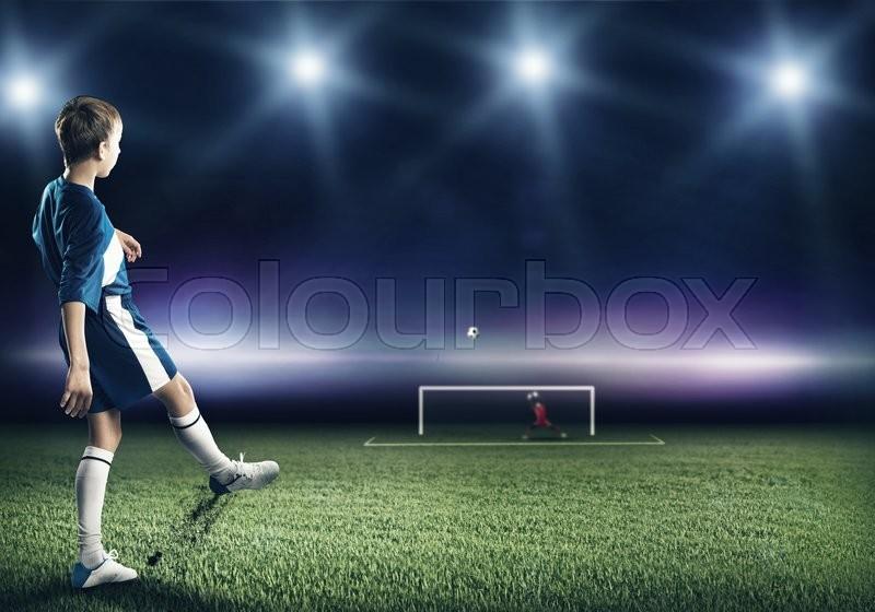 Kid boy football player on stadium kicking ball to gates, stock photo
