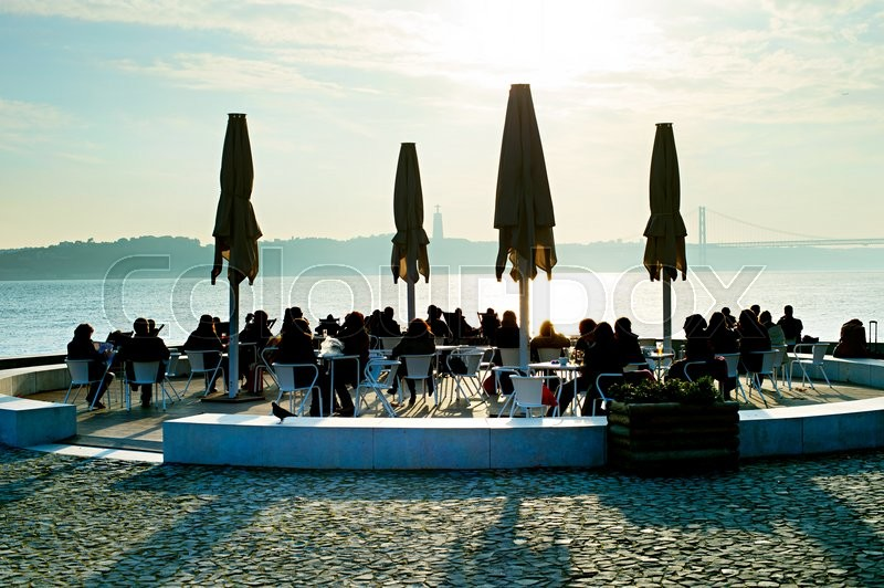 People in outdoor restaurant on embankment of Lisbon, Portugal, stock photo