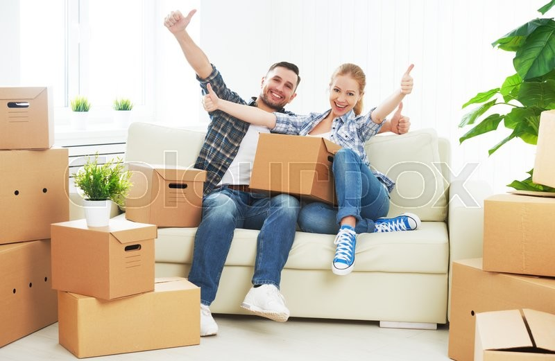 Moving to a new apartment. Happy family couple and a lot of cardboard boxes, stock photo