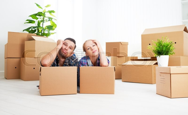 Moving to a new apartment. tired family couple and a lot of cardboard boxes, stock photo