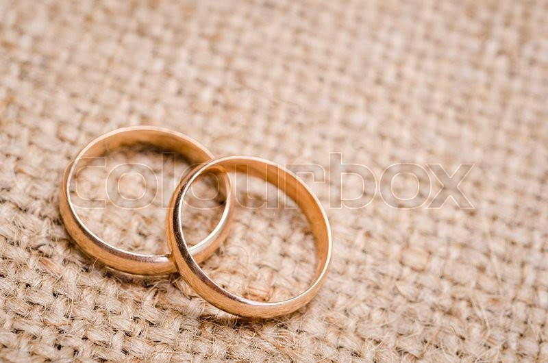 Two Gold Wedding Rings Lying On Brown Cloth Sacking Stock Photo