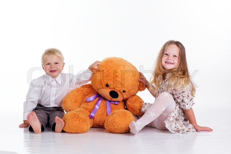 Beautiful child girl and boy are embracing big brown teddy bear, isolated on white, stock photo