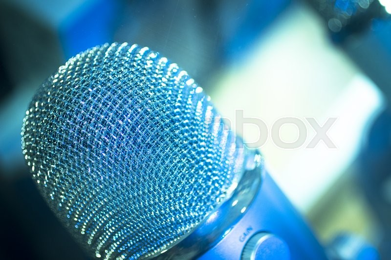 Professional studio voice recording concert singing microphone showing metallic body. Artistic color digital photo with shallow depth of focus and negative space and blurred background. , stock photo