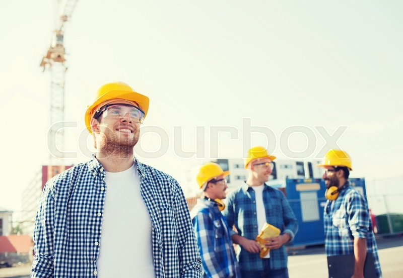 Business, building, teamwork and people concept - group of smiling builders in hardhats with clipboard outdoors, stock photo