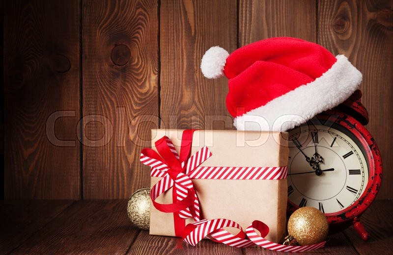 Christmas gift box, alarm clock and santa hat. View with copy space, stock photo